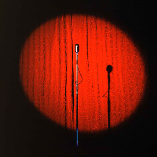standup comedy microphone red curtain