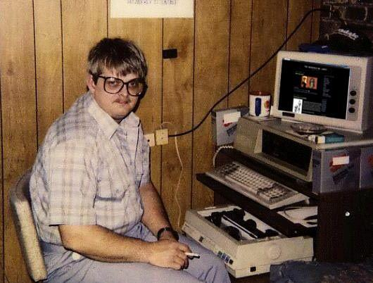 geek with computer in basement